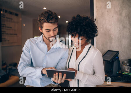 Two restaurant business partners standing together and looking at digital tablet. Man and woman using digital tablet in a cafe.