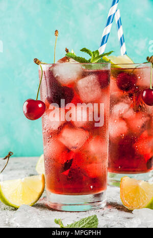 Summer iced refreshment drink, cherry cola lemonade or mojito cocktail in tall glass, on light blue and grey background copy space - Stock Photo