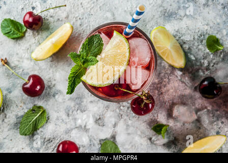 Summer iced refreshment drink, cherry cola lemonade or mojito cocktail in tall glass, on light blue and grey background copy space top view - Stock Photo