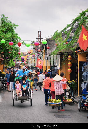Hoi An, Vietnam - February 17, 2016: Tourists on cycle rickshaws in the street of old city of Hoi An, Vietnam - Stock Photo