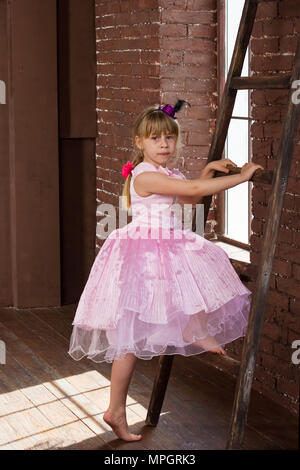 Girl 6 years old climbs a ladder in the room - Stock Photo