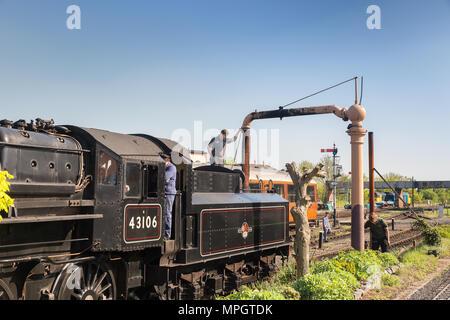 Vintage UK steam locomotive 43106 in the sidings, Kidderminster Severn Valley Railway station taking on water; train crew operate water crane, summer. - Stock Photo