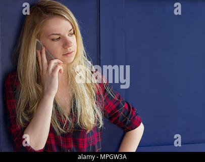 Pretty Woman Calling Someone Through Mobile Phone While Smiling at the Camera Against Blue Wall Background - Stock Photo