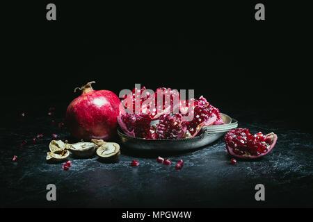 pomegranates in metal bowl - Stock Photo