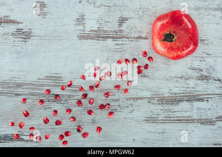 Pomegranate with seeds on wooden surface - Stock Photo