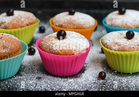 Muffins with black currant in silicone forms sprinkled with powdered sugar - Stock Photo