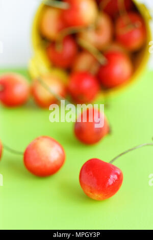 Cherries in a bucket on old wooden table - summer fruits - Stock Photo