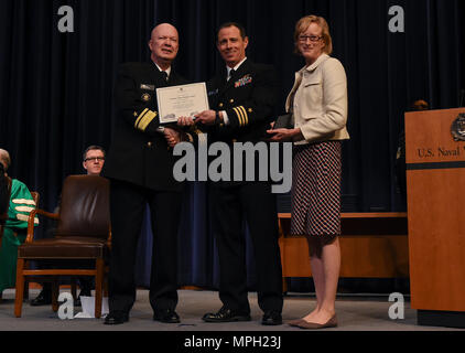 170228-N-RX668-129 NEWPORT, R.I. (Feb. 28, 2017) Cmdr. Ralph B. Shield (center) is presented with a certificate by Rear Adm. Jeffrey A. Harley (left), president, U.S. Naval War College (NWC), and Wendy Skinner (right), director of development, NWC Foundation for being recognized as College of Naval Warfare's (CNW) Presidential Honor Graduate at NWC in Newport, Rhode Island. Seventy-four students from the CNW and College of Naval Command and Staff were recognized for their achievements and received either a Master of Arts degree in National Security and Strategic Studies or Master of Arts degre - Stock Photo