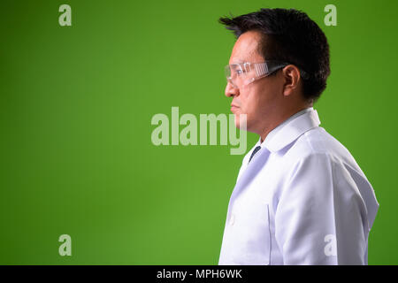 Mature Japanese man doctor wearing protective glasses against green background - Stock Photo