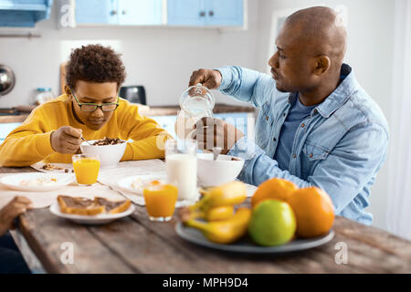 Pleasant young man pouring milk while son eating cereals - Stock Photo