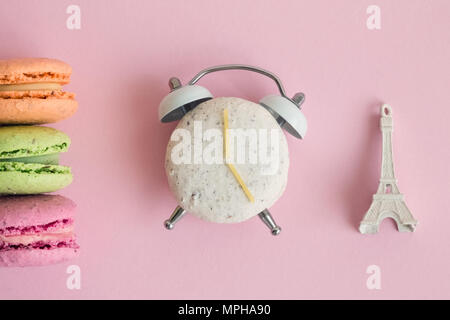 Flat lay of colorful macarons and Eiffel Tower miniature model on pastel pink background. One of macaroons in shape of alarm clock with clock hands ma - Stock Photo