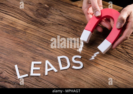 Businessperson Attracting White Lead Text With Horseshoe Magnet Over Wooden Desk - Stock Photo