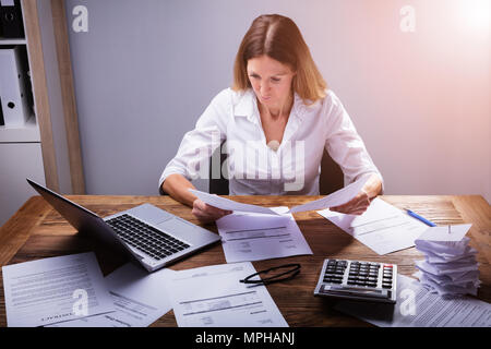 Businessperson Calculating Invoice With Calculator In Office - Stock Photo