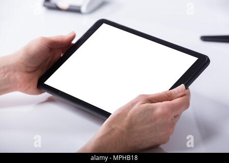 Woman's Hand Using Digital Tablet With Blank White Screen - Stock Photo