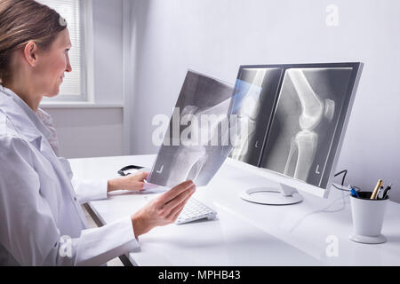 Mature Female Doctor Examining Knee X-ray In Clinic - Stock Photo