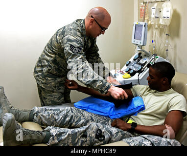 Staff Sgt. Jonathan Flannigan, NCO in charge of the apheresis element with the 379th Expeditionary Medical Group, wraps a pressure cuff around the arm of Senior Airman Jordan Marshall, an aerospace medical technician with the 379th EMDG, at Al Udeid Air Base, Qatar, March 7, 2017. Marshall volunteered to donate blood platelets which are essential to Airmen in combat zones without access to immediate medical treatment.  (U.S. Air Force photo by Senior Airman Cynthia A. Innocenti) - Stock Photo