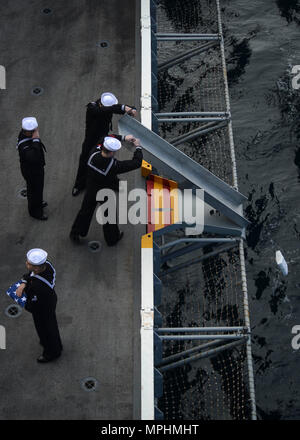 170315-N-KR702-279 PACIFIC OCEAN (March 15, 2017) Sailors assigned to the aircraft carrier USS Nimitz (CVN 68) render honors during a burial at sea. Nimitz commited 16 Sailors, one soldier and one civilian during the first burial at sea ceremony held aboard the ship in more than 2 years. Nimitz is underway conducting a composite training unit exercise in preparation for an upcoming 2017 deployment. (U.S. Navy photo by Mass Communication Specialist 2nd Class Holly L. Herline/Released) - Stock Photo