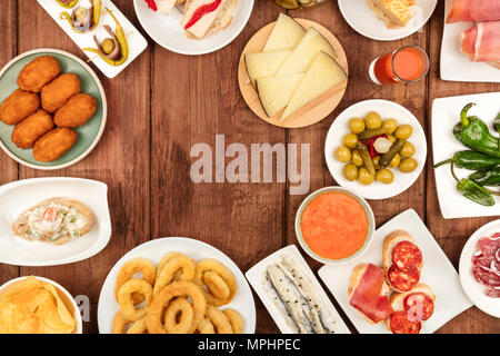 Food of Spain. An overhead photo of many different Spanish tapas, shot from above on a dark rustic texture. Gazpacho, cheese, olives, croquettes, boqu - Stock Photo