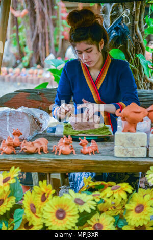 Lopburi, Thailand - July 21, 2013: Craftswoman making pottery of dolls and sculpture of animals from clay in the workshop in Lopburi, Thailand - Stock Photo