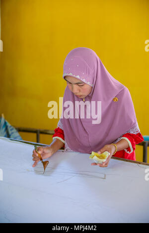Krabi, Thailand - May 2, 2015: Muslim woman drawing on pattern line on Batik fabric by liquid candle inn her home in Krabi, Thailand - Stock Photo