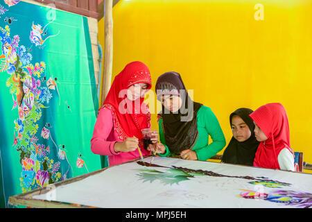 Krabi, Thailand - May 2, 2015: Beautiful Muslim woman wearing red hijab painting pattern on Batik fabric in her home in Krabi, Thailand - Stock Photo