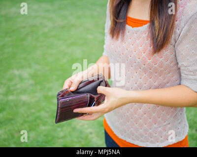 Unhappy bankrupt woman with empty wallet. Young woman shows her empty wallet. Bankruptcy - Stock Photo