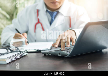 doctor searching information from computer and writing on notebook on working table - Stock Photo