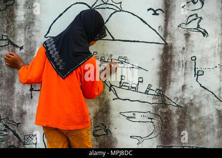 Krabi, Thailand - May 3, 2015: Muslim girl wearing black hijab drawing graphic image on wall of ruined house in Krabi, Thailand - Stock Photo
