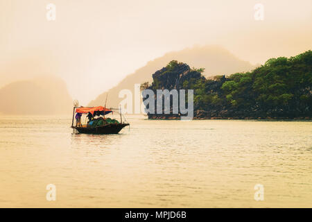 Fishing boat at Ha Long Bay, Vietnam at sunset. Limestone islands on the background - Stock Photo