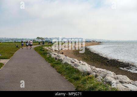 People walking along Poole harbour coast on a summers morning, Dorset, United Kingdom - Stock Photo