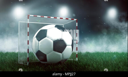 Soccer ball in small goal on green lawn against stadium lights, viewed from low angle. Football championship concept. 3d Rendering - Stock Photo