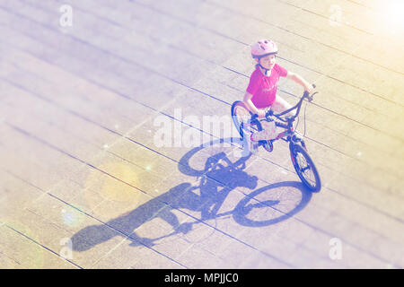 A young child having fun on a bicycle, on a sunny day creating a long shadow. October 2015 --- Image by © Paul Cunningham - Stock Photo