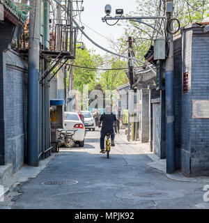 A Chinese man riding a bicycle on a backstreet in Beijing. Overlooked by a surveillance camera. - Stock Photo