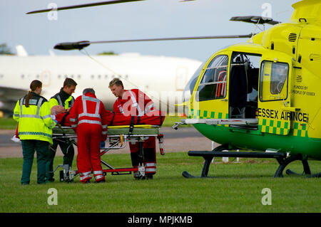 Essex Air Ambulance helicopter Eurocopter EC135 G-SSXX with paramedics and ambulance crew dealing with a patient transfer on a trolley - Stock Photo