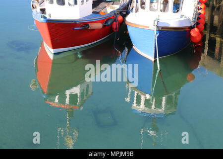 Close up of fronts of one small red and one small blue lobster boat in harbour with reflections of bows in water - Stock Photo