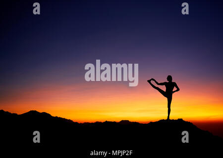 Fit Man in silhouette doing yoga balance pose at beautiful orange sunset sky background