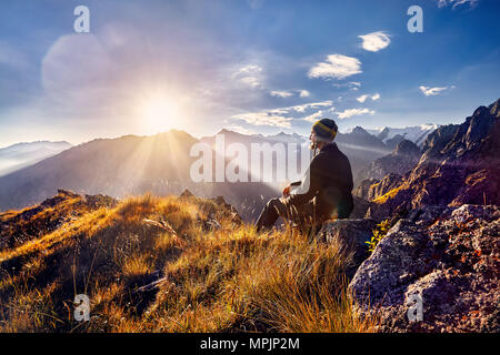 Tourist in Nepali hat sitting on the hill and looking at sunrise in the mountains - Stock Photo