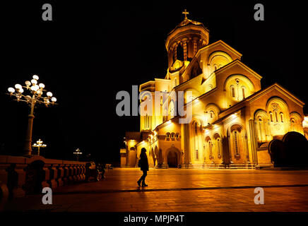 Woman silhouette near The Holy Trinity Cathedral or Tsminda Sameba Church at night in Tbilisi, Georgia - Stock Photo