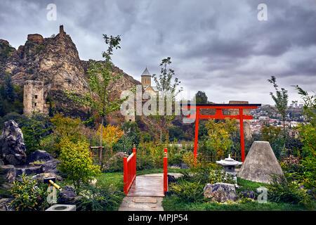 Japanese garden and old castle Narikala at overcast cloudy sky in botanical garden of Tbilisi, Georgia - Stock Photo