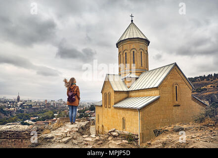 Tourist woman near Cathedral in Old medieval castle Narikala at overcast cloudy sky in Tbilisi, Georgia - Stock Photo