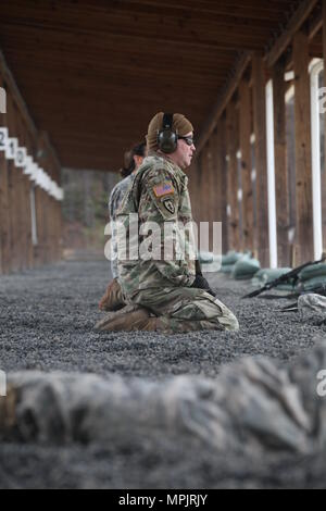 US Army Sgt. 1st Class Sean Foley, 982nd Combat Camera Company Airborne, scans his target after zeroing the Close Combat Optic on his M16 rifle on Fort Jackson, S.C., March 18, 2017. The 982nd Combat Camera Company (Airborne) is one of only two combat camera companies in the U.S. Army tasked with providing the Office of the Secretary of Defense, Chairman of the Joint Chiefs of Staff, and the military departments with a directed imagery capability in support of operational and planning requirements through the full range of military operations.. (U.S. Army Photo by SPC Joshua Talley) - Stock Photo