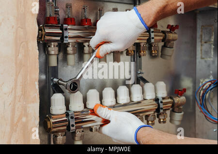 Installation of home heating. A worker fixes the underfloor heating manifold. - Stock Photo
