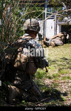 Cpl. Steve Hardin, a team leader with Echo Company, Battalion Landing Team, 2nd Battalion, 5th Marines, 31st Marine Expeditionary Unit, holds security while participating in a mechanized raid as part of Amphibious Integrated Training (AIT) at Marine Corps Base Camp Butler, Okinawa, Japan, March 15, 2017. AIT assimilates the capabilities of the 31st MEU Marine Air-Ground Task Force and the amphibious ships of the Bonhomme Richard Amphibious Ready Group to conduct ship to shore operations. As the Marine Corps' only continuously forward-deployed unit, the 31st Marine Expeditionary Unit's air-grou - Stock Photo