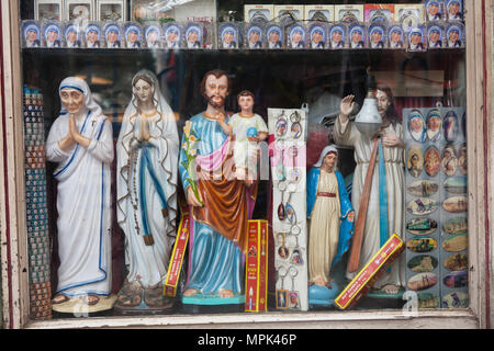India, West Bengal, Kolkata, Window display of a shop in selling Christian icons and Mother Teresa souvenirs and memorabilia. - Stock Photo