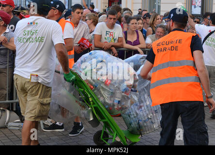LE MANS, FRANCE - JUNE 16, 2017: Worker Man Collecting Garbage with cans and plastic on the street at parade of pilots - Stock Photo