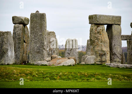 view of circle of sarsen trilithon stones with tenon joint on one on left and banking with centre altar stones and bluestones stonehenge wiltshire eng - Stock Photo