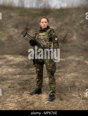 170320-M-IN448-243 CAPU MIDIA, ROMANIA (March 20, 2017)— Romanian Sailor Cpl. Pintilie Madalina, a communications specialist, poses for a portrait during a live-fire shoot with U.S. Marines of the 24th Marine Expeditionary Unit (MEU), Female Engagement Team, at Capu Midia training grounds in Romania March 20, during exercise Spring Storm 2017. The Marines trained for three days with their female Romanian counterparts in radio communication, detainee handling, personal security detail, tactical site exploitation and more, culminating in a live-fire rifle and pistol swap between the two forces.  - Stock Photo