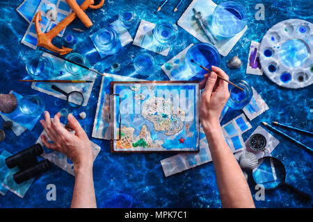 Artist painting a fantasy island map. Underwater still life concept. Creative artist workplace flat lay. - Stock Photo