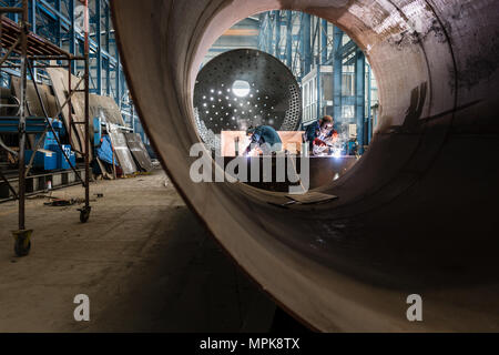 Two workers welding in a factory manufacturing boilers  - Stock Photo