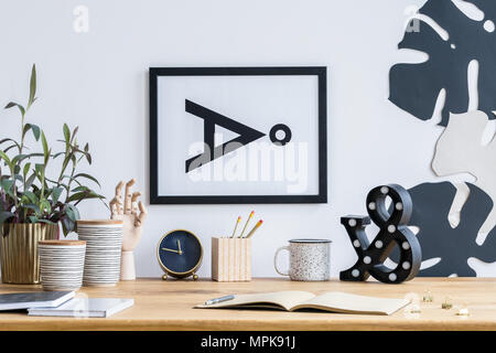 Notebook and gold clock on wooden desk in study area with plant, pots and simple poster - Stock Photo